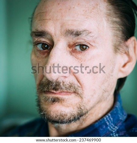 Portrait Of Serious Sad Old Adult Expressive Man With Beard Looking At Camera On Green Wall Background - stock photo