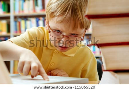 Portrait of serious schoolkid working with laptop in the library - stock photo