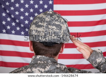 Portrait Of Serious Solider Standing In Front Of Us Flag Saluting - stock photo
