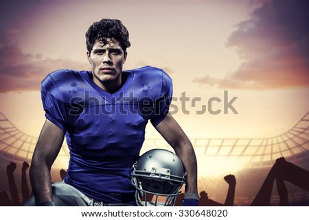 Portrait of serious sportsman with hand on knee holding helmet against football stadium with cheering crowd