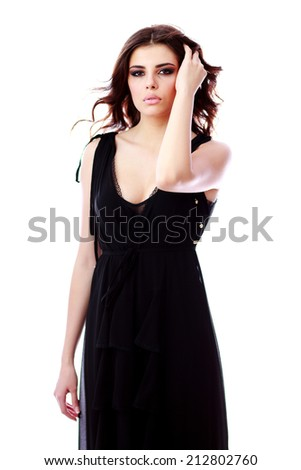 Portrait of serious woman in black dress over white background