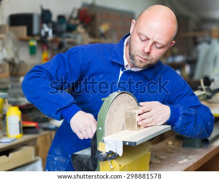 Portrait of serious woodworker working on a machine at wood workshop - stock photo