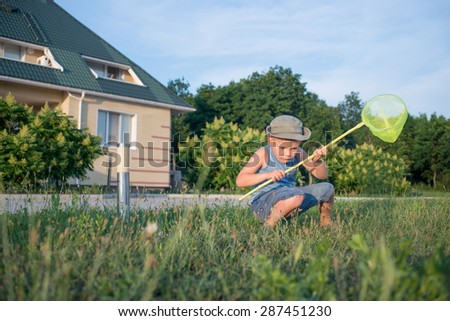 Portrait of Serious Young Boy with Bug Net Crouching in Long Grass on Lawn Outdoors in Summer - stock photo