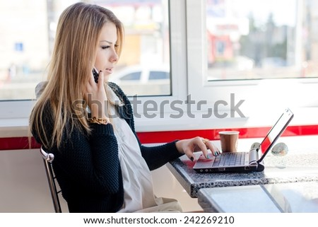 portrait of serious young business woman talking on the mobile phone working on a laptop pc computer sitting in a restaurant - stock photo
