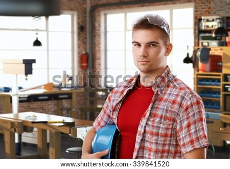 Portrait of serious young casual caucasian handyman standing at DIY workshop, looking at camera, hardhat under arm. - stock photo