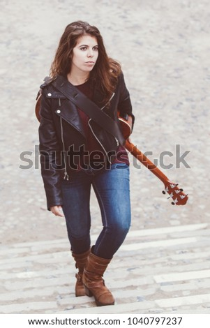 Portrait Of Serious Young Female Musician Walking Upstairs In Street And Carrying Guitar On Back