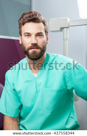 Portrait of serious young handsome attractive male doctor with beard in green costume sitting in dental clinic. Face expressions, emotion, health care, medicine. - stock photo
