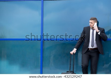 Portrait of serious young man on business trip standing with his luggage while talking on smartphone in front of modern glass building outdoors. Travelling guy making call. Copy space