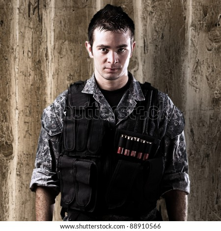 portrait of serious young soldier against a wooden wall