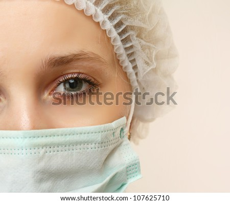 Portrait of serious young woman doctor with mask and cap - stock photo
