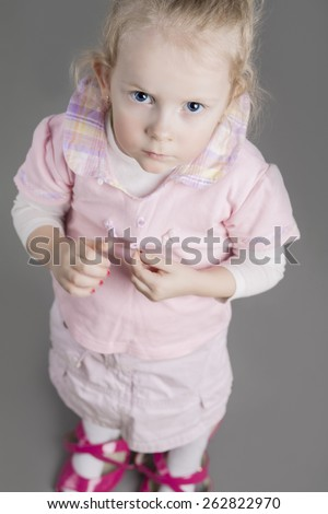 Portrait of Seriously Looking Caucasian Girl Wearing Mother's Parental High Heel Shoes. Thoughtful facial Expression. Vertical Image - stock photo