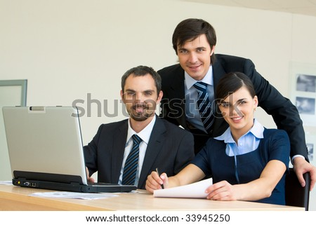 Portrait of several confident colleagues looking at camera with smiles at workplace