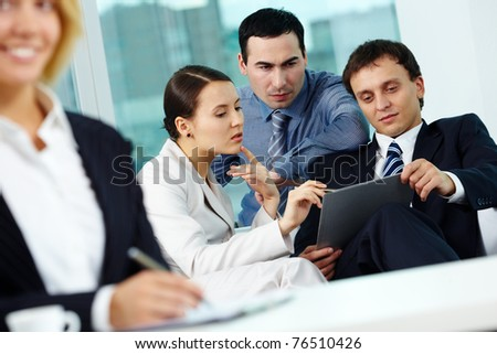 Portrait of several employees discussing plan in office - stock photo