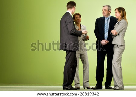 Portrait of several smart associates talking to each other after meeting or conference - stock photo