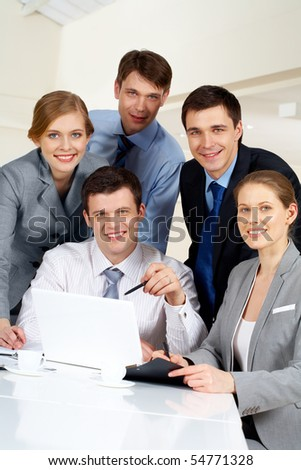 Portrait of several successful co-workers looking at camera with smiles at workplace - stock photo