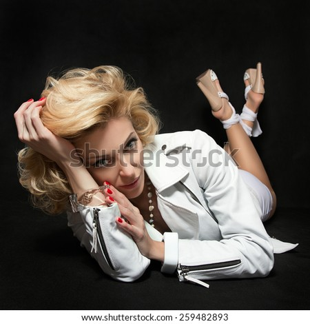 Portrait of sexual adult blond woman wearing white dress and leather jacket lying on black background