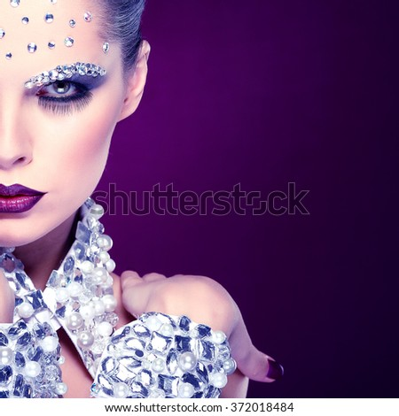 Portrait of sexual beautiful girl with strasses on face, on a violet background - stock photo
