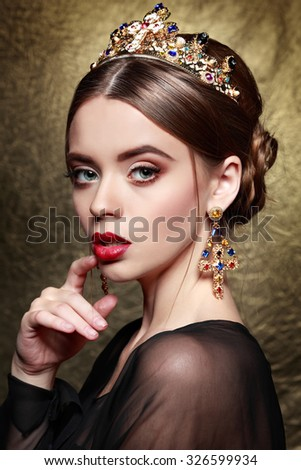 Portrait of sexual stylish girl in a crown on a gold background.Accessorys. - stock photo