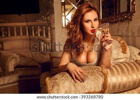 Portrait of sexual young brunette lady with glass of martini. Seductive woman. Sexual woman. the concept of seduction, pleasure and desire - stock photo