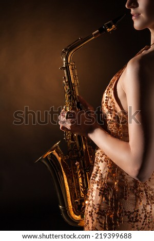 Portrait of sexual young woman posing with saxophone at studio. - stock photo