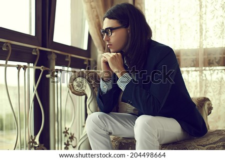 portrait of sexy attractive stylish model man with long hair in costume sitting on the sofa in classic interior