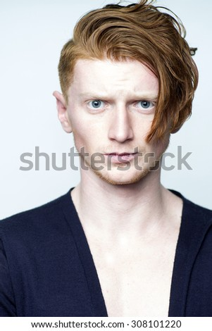Portrait of sexy attractive young guy model with red hair in black jersey looking forward standing in studio on white background copyspace, vertical picture - stock photo
