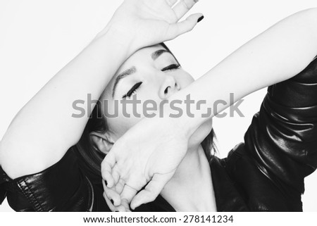 Portrait of sexy beautiful young blonde woman in leather jacket with hands over her face and closed eyes - stock photo