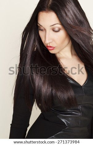 Portrait of sexy beautiful young brunette woman in black leather dress - stock photo