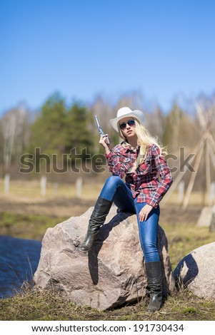 Portrait of Sexy Blond Cowgirl with Gun outside. Vertical Image - stock photo