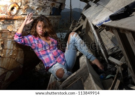 portrait of sexy blond woman in jeans posing in from of shipwreck - stock photo