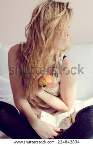 portrait of sexy blonde girl having fun happy holding book & big red apple sitting on white bed on light copy space background - stock photo