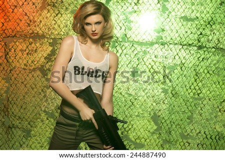 portrait of sexy blonde  with gun against camouflage net  - stock photo