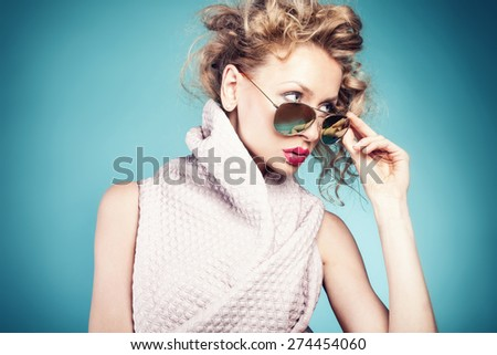 Portrait of sexy blonde woman with curly hair. Girl wearing sunglasses. Blue background. - stock photo