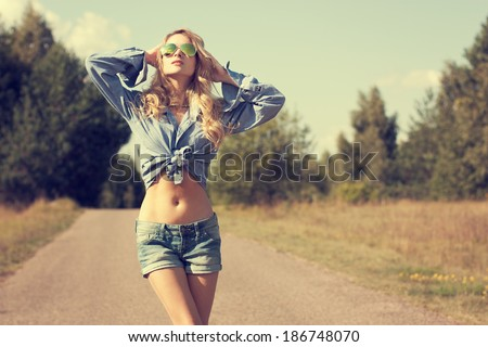 Portrait of Sexy Blonde Woman with Hands behind her Head Walking on Country Road and Looking to the Sky. Toned Photo. Street Style. - stock photo