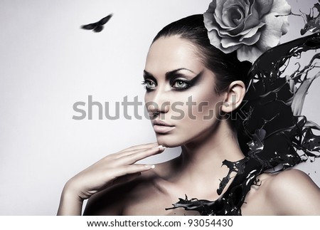 portrait of sexy brunette woman with black splash and rose