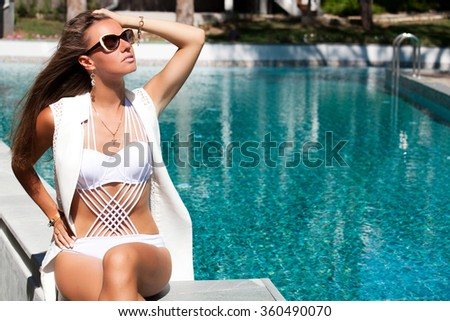 Portrait of sexy cheerful woman relaxing at the luxury poolside. Girl at travel spa resort pool. Summer luxury vacation. - stock photo