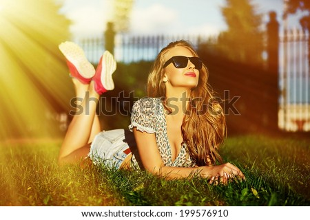 portrait of sexy cute funny young stylish smiling woman girl model in bright modern cloth with perfect sunbathed body outdoors lying in the park on green grass in jean shorts in glasses - stock photo