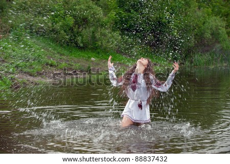 Portrait of sexy, fresh young girl enjoys playing in the river