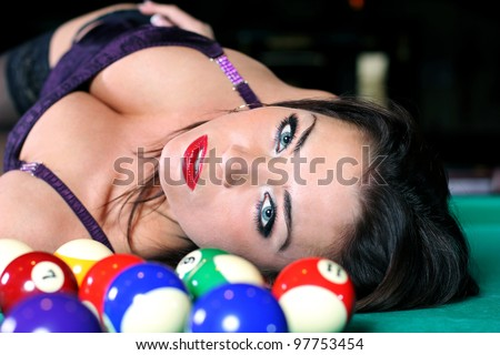 Portrait of sexy girls lying on the table for a game of billiards - stock photo