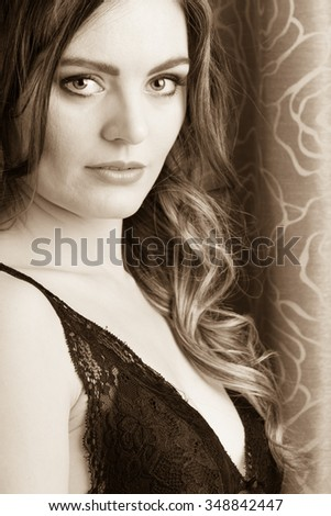 Portrait of sexy gorgeous woman by curtain. Attractive sensual young girl with long hair in lingerie. Female fashion. Sepia.