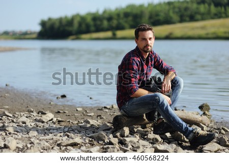 Portrait of sexy handsome man model doing a fashion shoot outdoor on the beach of river