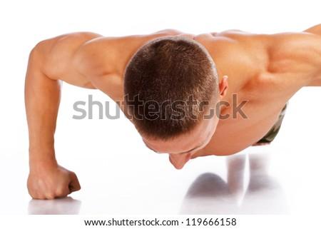 Portrait of sexy man doing push up in studio - stock photo