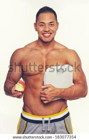 Portrait of sexy man eating apple - stock photo