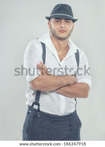 Portrait of sexy man posing in studio in hat - stock photo