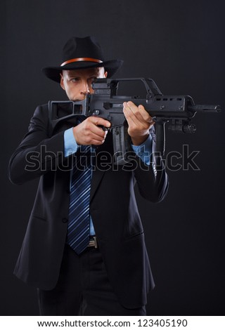 Portrait of sexy man posing in studio in suit with gun