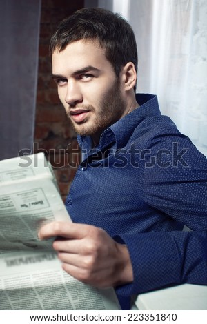 Portrait of sexy man reading newspaper - stock photo