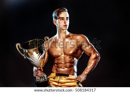 Portrait of sexy muscular guy posing topless with cup in hands and looking away. Copyspace.