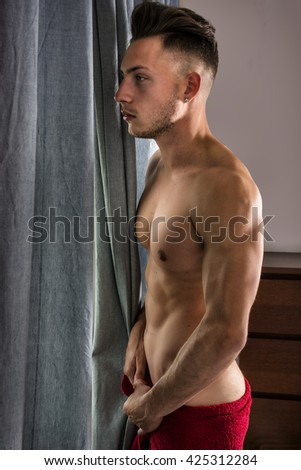 Portrait of sexy shirtless man looking out of window during the day - stock photo