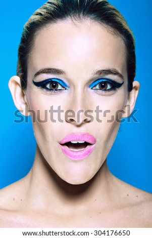 Portrait of sexy surprised woman against light blue background - stock photo