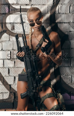 portrait of sexy topless blonde with airsoft guns posing against wall with graffiti - stock photo